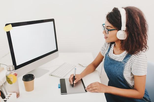 Inspirierte junge frau im gestreiften hemd, das computerbildschirm betrachtet und mit tablette arbeitet