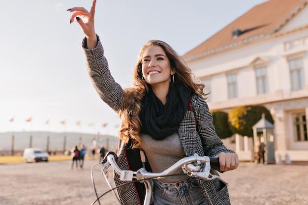 Inspirierte junge frau im schwarzen schal, der auf fahrrad durch europäische stadt reitet