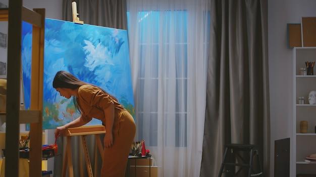 Inspirierte junge malerin in ihrer werkstatt, die ein meisterwerk macht.