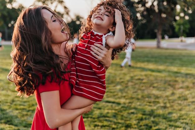 Inspirierte junge mutter, die tochter mit lächeln betrachtet. außenporträt der glücklichen familie, die sommerwochenende im park genießt.