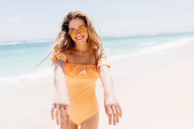 Inspirierte langhaarige frau, die im sommerwochenende im freien kühlt und an der seeküste aufwirft. das schöne gebräunte mädchen trägt einen stilvollen orangefarbenen badeanzug im resort.