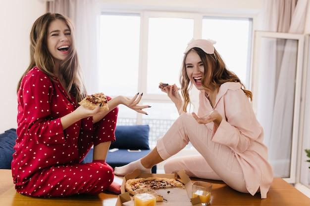 Inspirierte mädchen, die auf tisch sitzen und pizza essen. lachende junge damen in stilvollen pyjamas, die herumalbern und das frühstück genießen.