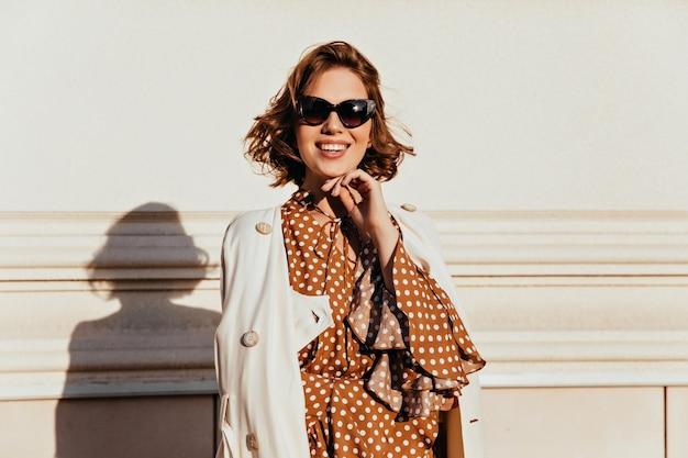 Inspirierte stilvolle frau in der sonnenbrille, die neben wand steht. außenaufnahme des lachenden blithesome mädchens mit braunen haaren.