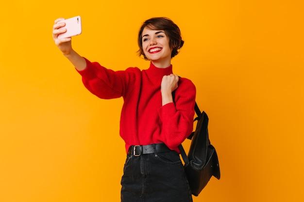 Inspirierte trendige frau mit kurzen haaren, die selfie nimmt