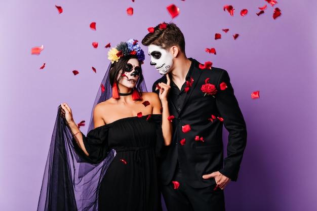 Inspirierte vampirbraut, die im schwarzen kleid aufwirft. totes paar, das hochzeit in halloween feiert.