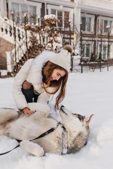 Inspirierte weiße dame im hut, die mit husky auf dem schnee herumalbert. foto im freien der lachenden jungen frau, die mit ihrem hund im hof spielt.