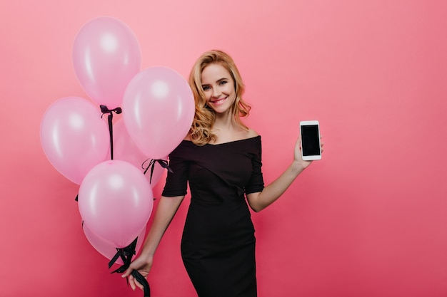 Inspirierte weiße frau mit gewellter frisur, die neues smartphone zeigt. positive kaukasische dame, die bündel der rosa luftballons der partei hält und lächelt.