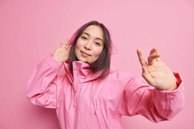 Inspirierte zufriedene asiatische frau genießt jede note der lieblingsmusik bewegt sich rhythmisch mit erhobenen armen, trägt stereo-kopfhörer mit perfektem klang an den ohren, die über rosafarbener wand isoliert sind. fang meine welle