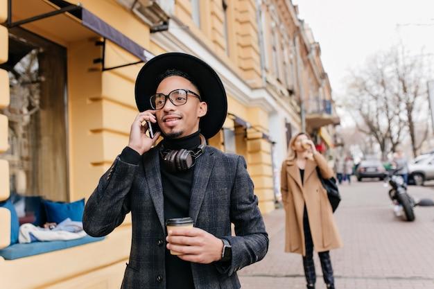 Inspirierter afrikanischer junge, der kaffee auf der straße trinkt. außenporträt des sorglosen schwarzen männlichen modells, das latte genießt und am telefon spricht.