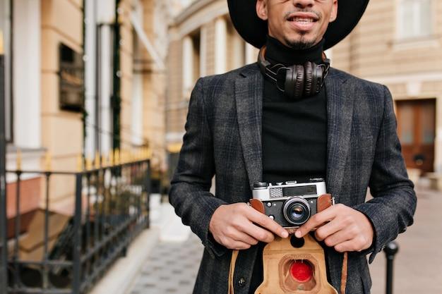 Inspirierter afrikanischer mann trägt schwarzes hemd, das auf straße mit kamera in händen steht. außenaufnahme eines gut gekleideten fotografen.