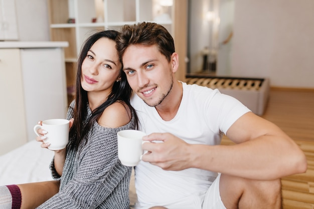 Inspirierter kaukasischer mann, der am sonntagmorgen kaffee mit freundin trinkt
