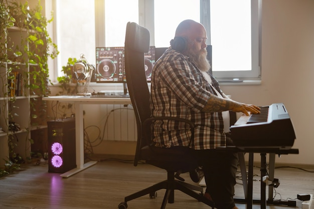 Inspirierter komponist schreibt musik, die synthesizer im heimstudio spielt