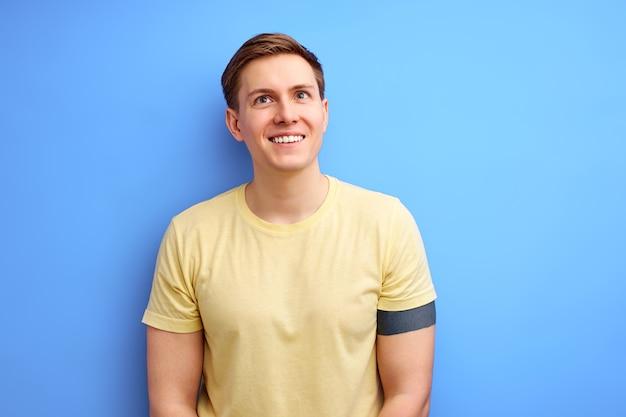 Inspirierter mann in lässiger t-shirt-kleidung steht in der betrachtung und schaut lächelnd auf. isoliert über blauem studiohintergrund. lebensstil, menschen, menschliches gefühlskonzept