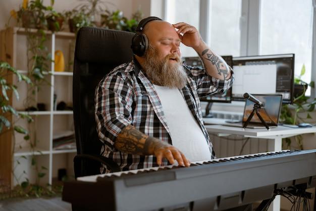 Inspirierter mann komponist mit kopfhörer schreibt musik auf synthesizer im heimstudio