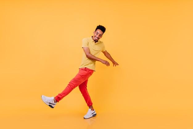 Inspirierter schwarzer kerl in der hellen freizeitkleidung, lustiges tanzen. lachendes afrikanisches männliches modell im gelben t-shirt und in den roten hosen, die herumalbern.