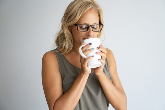 Inspirierter weiblicher büroangestellter, der kaffeepause genießt.