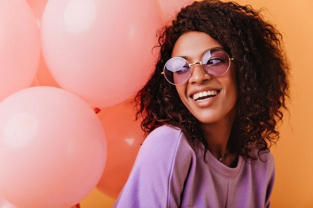 Inspiriertes afrikanisches mädchen, das gute gefühle in ihrem geburtstag ausdrückt. blithesome lockige dame, die mit rosa luftballons aufwirft.