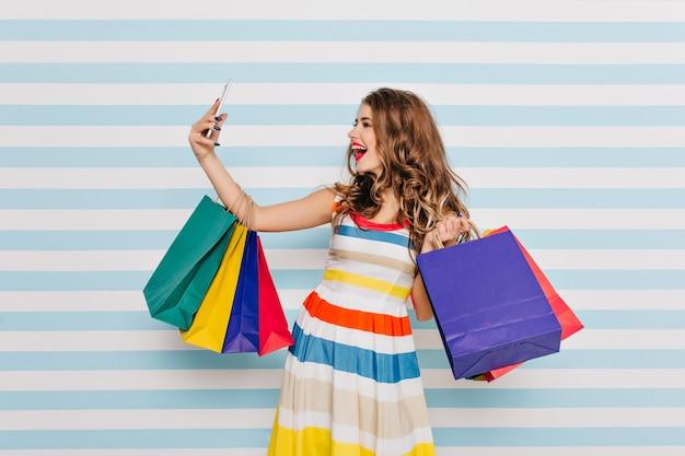 Inspiriertes braunhaariges mädchen, das nach dem einkaufen und lachen selfie macht. stilvoller kaukasischer weiblicher shopaholic, der taschen hält und sich selbst fotografiert.