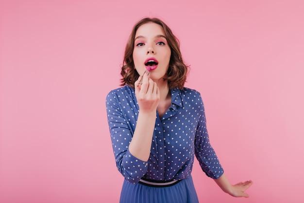 Inspiriertes brünettes mädchen mit dunklen augen unter verwendung des rosa lippenstifts. innenfoto der modischen jungen dame mit der kurzen frisur, die ihr make-up tut.