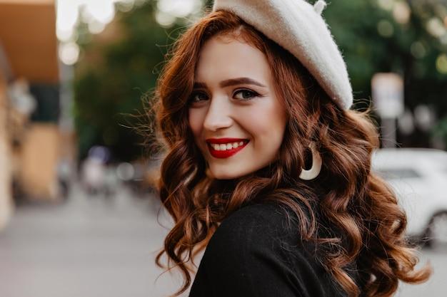 Inspiriertes französisches model, das auf der straße lacht. ingwer-mädchen in der trendigen baskenmütze, die im herbsttag draußen geht.