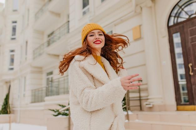 Inspiriertes ingwermädchen, das auf der straße tanzt. enthusiastische kaukasische dame, die spaß im winter hat.