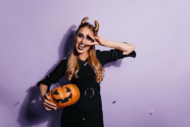 Inspiriertes kaukasisches mädchen in magischer kleidung, die auf lila wand aufwirft. stilvoller weiblicher vampir, der halloween-kürbis mit lächeln hält.