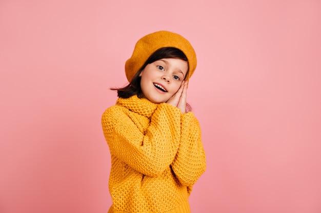 Inspiriertes kind, das auf rosa wand aufwirft. kurzhaariges jugendliches mädchen.