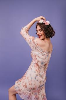 Inspiriertes lustiges mädchen im trendigen kleidertanzen. nette kaukasische dame mit blumen auf ihrem haar stehend.