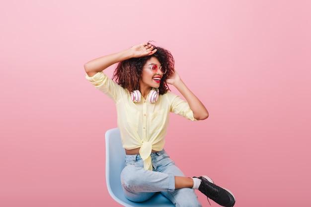Inspiriertes schlankes mädchen im gelben weinlesehemd, das sich auf stuhl erstreckt. innenporträt der reizenden lockigen afrikanischen dame in den schwarzen turnschuhen, die mit lächeln wegschauen.