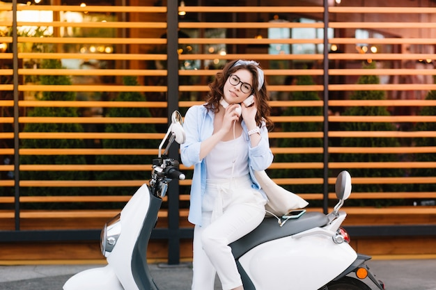 Inspiriertes schlankes mädchen mit stilvollem haarschnitt, das auf roller sitzt und bereit ist, am wochenende durch die stadt zu fahren