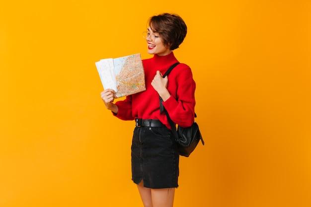 Inspiriertes weibliches modell, das karte betrachtet