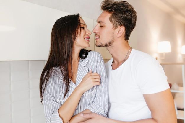 Inspiriertes weibliches modell mit hübscher frisur, die ehemann am kalten morgen küsst