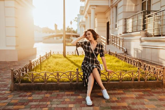 Inspiriertes weißes mädchen, das fotoshooting im sonnigen herbstmorgen genießt und lächelt. außenfoto der begeisterten modischen frau im karierten kleid.