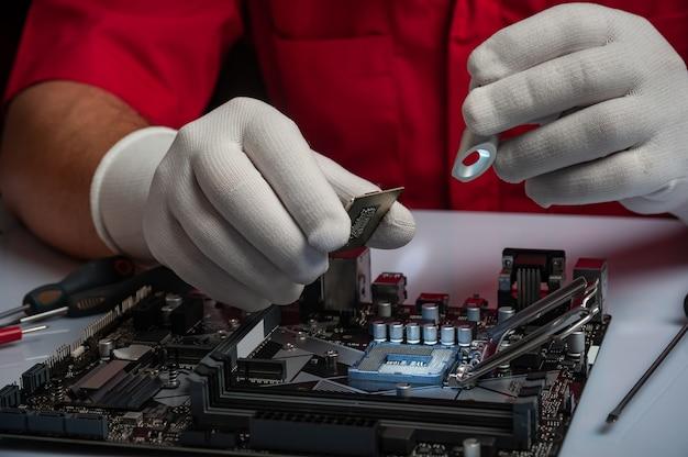 Installation der multi-core-cpu auf dem computer-motherbord. pc-montage oder upgrade auf modernen chipsatz. elektronisches konzept mit prozessor, wenig licht