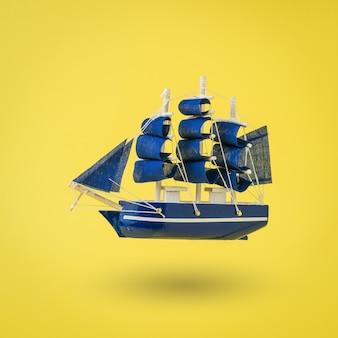 Installation eines alten schiffes mit segeln auf einer gelben oberfläche. ein traum wird wahr.