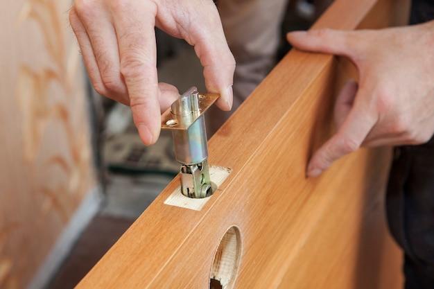 Installation verriegelte innentürgriffe, holzarbeiter hände installieren schloss.