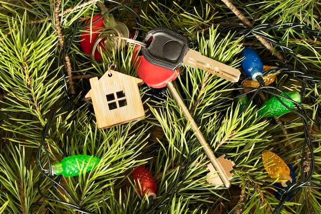 Installation von geschenk, schlüssel, haus und figuren auf dem tisch, draufsicht. herzlichen glückwunsch zum neuen haus. geschenk zu weihnachten. mietwohnungen für die feier des neujahrsferienkonzepts.