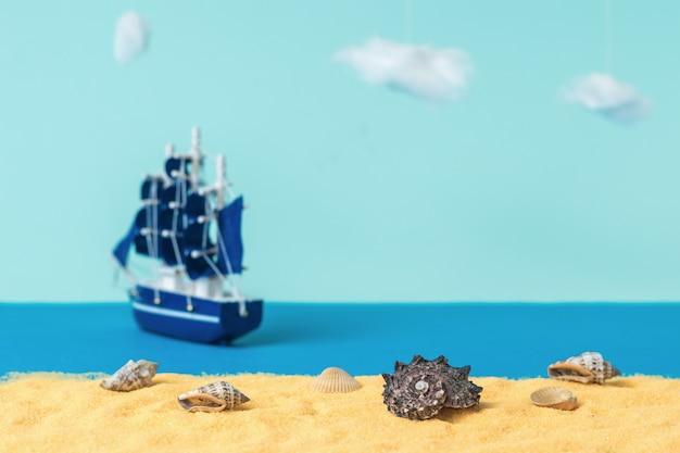 Installation von muscheln an einem sandstrand vor dem hintergrund eines wegsegelnden segelschiffs. das konzept von reisen und abenteuer. installation.