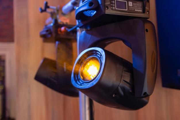 Installation von professioneller ton-, licht-, video- und bühnentechnik für ein konzert. bühnenbeleuchtungsgeräte werden zum anheben an einer traverse festgeklemmt. flightcases mit kabeln.