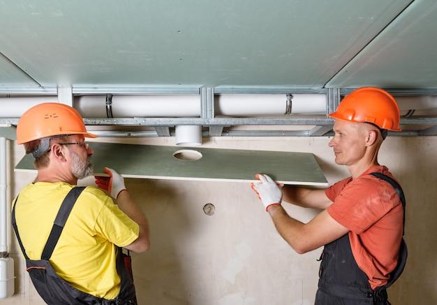 Installation von trockenbauarbeiten arbeiter installieren die gipskartonplatte mit einem entlüftungsloch