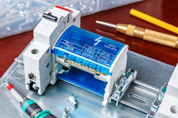Installiert auf din-schiene auf montageplatte, automatischem leistungsschalter und kabelklemme mit installationswerkzeug. montage der schalttafel