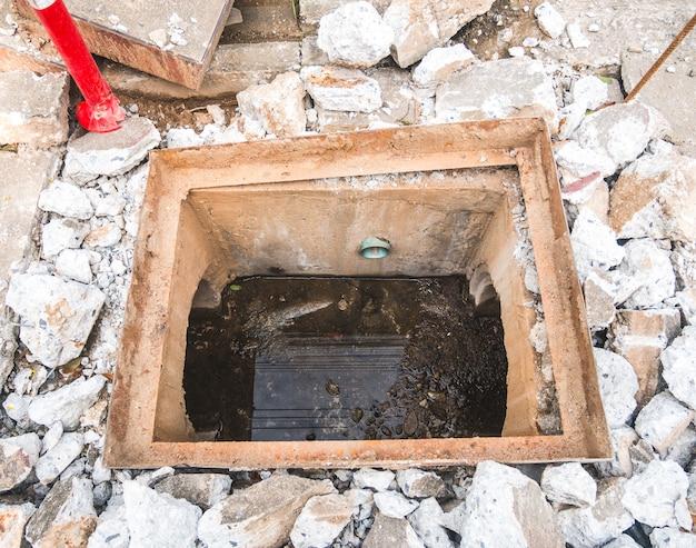 Instandhaltung der abwasserkanal-reparaturstelle auf der straße.