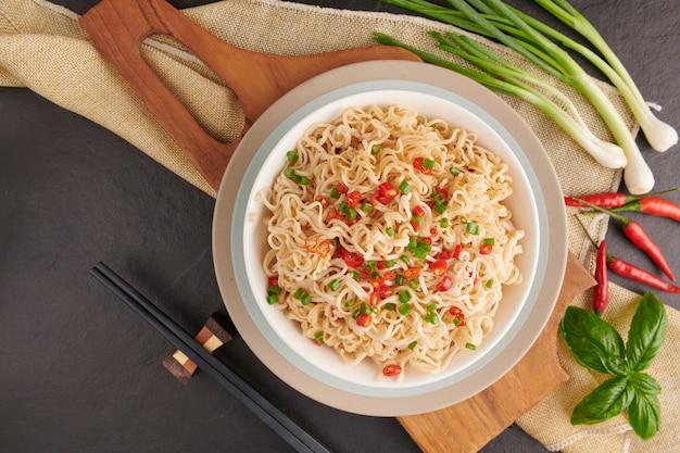 Instant-nudeln und suppe, um geschnittene zwiebeln und paprika zu essen und das schweinefleisch hineinzulegen. ansicht von oben