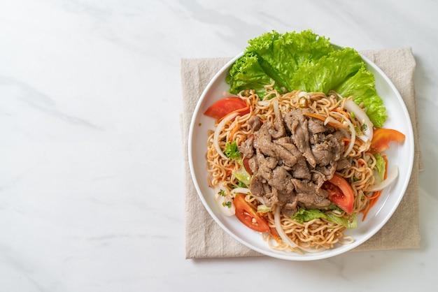 Instant-nudeln würziger salat mit schweinefleisch auf weißem teller. asiatischer essensstil