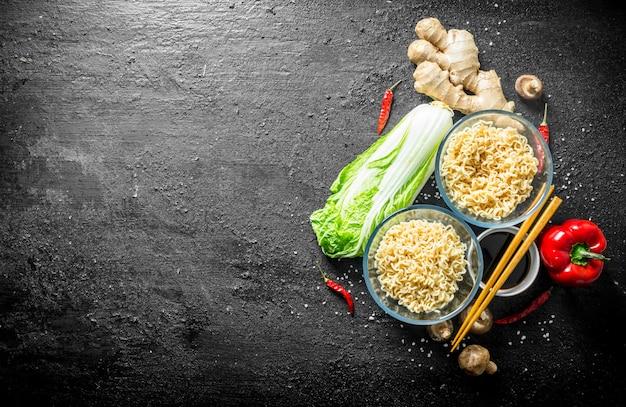 Instantnudeln mit ingwer, pilzen, paprika, pekinger kohl und sojasauce. auf schwarzem rustikalem hintergrund
