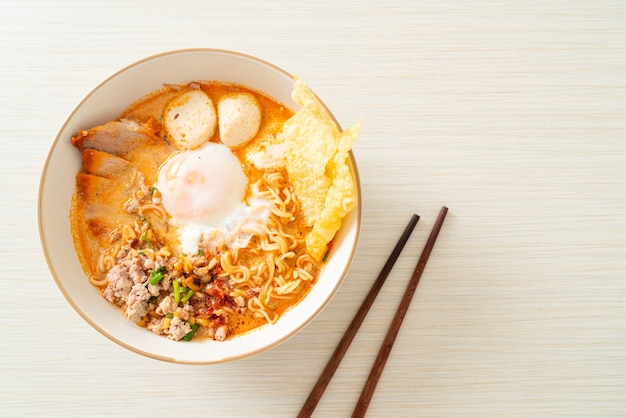 Instantnudeln mit schweinefleisch und frikadellen in scharfer suppe oder tom yum nudeln nach asiatischer art
