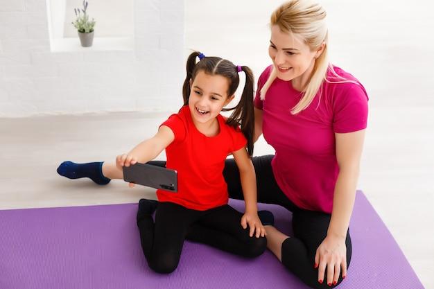 Instruktor und mädchen entspannen sich nach dem training auf der matte, benutzen das telefon im fitnessstudio, um videos anzuschauen, wie man sprungübungen macht?