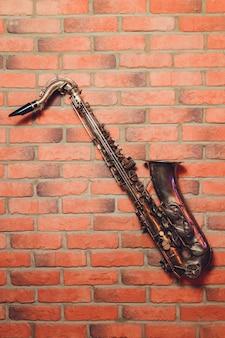 Instrument der klassischen musik des saxophons auf maurerarbeitwand