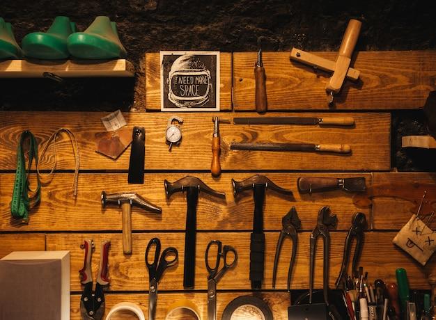Instrumente an der holzwand in der schuhwerkstatt.