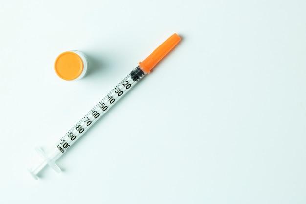 Insulin spritzt die nadel ein, die auf weißem hintergrund lokalisiert wird